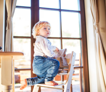 Little toddler boy climbing on wooden highchair at home. Domestic accident. Dangerous situation at home.