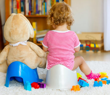 Closeup of cute little 12 months old toddler baby girl child sitting on potty. Kid playing with big plush soft toy. Toilet training concept.
