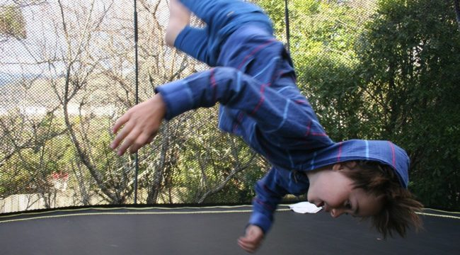 The little boy is doing exercise on a trampoline