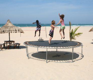 three children on trampoline on beach