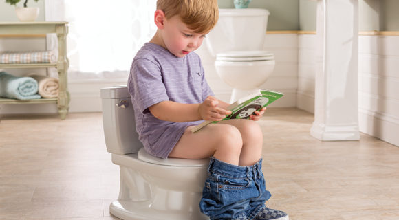 A little boy sits on potty and reads a book