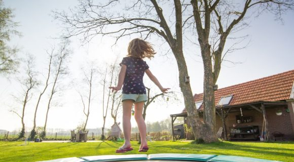 The little girl jumps on a trampoline in safety