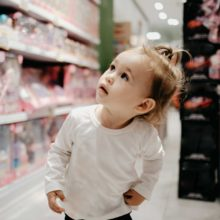 baby girl looks at products in shop
