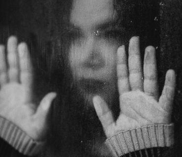 sorrow woman behind window
